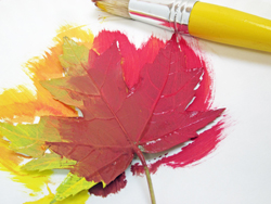 Painting a fall leaf with acrylic paint.